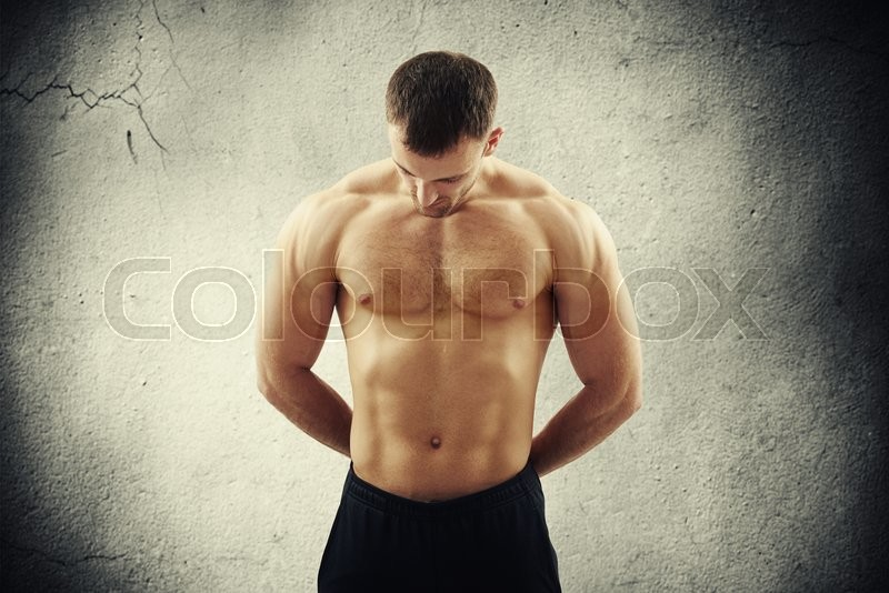 Stock image of 'Bare-chested young muscular man in black pants is looking down standing over old concrete wall with vignette'