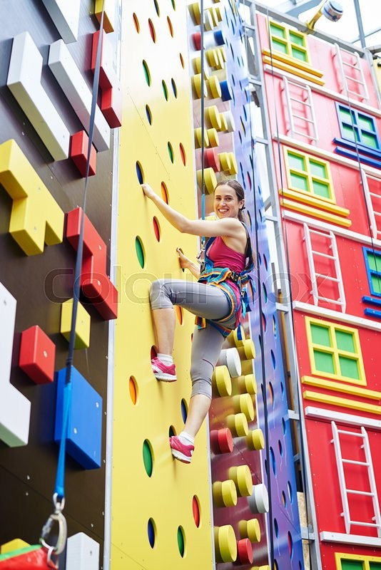 Stock image of 'A smiling young woman in safety harness is climbing on a high rock-climbing wall in gym'