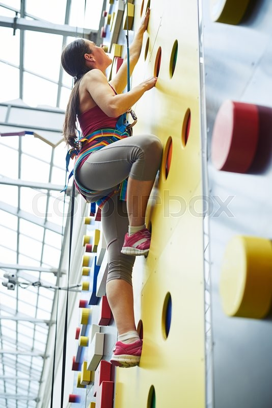 Stock image of 'A young woman in safety harness is climbing up on the wall in rock-climbing center'
