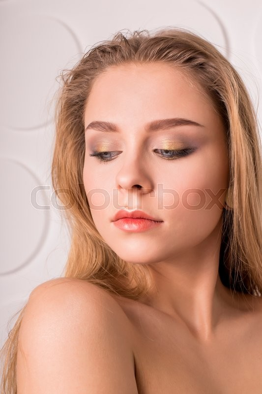 Stock image of 'Portrait of Beautiful Young Woman with Clean Fresh Skin and Nude MakeUp. Isolated on Grey Background. Close up'