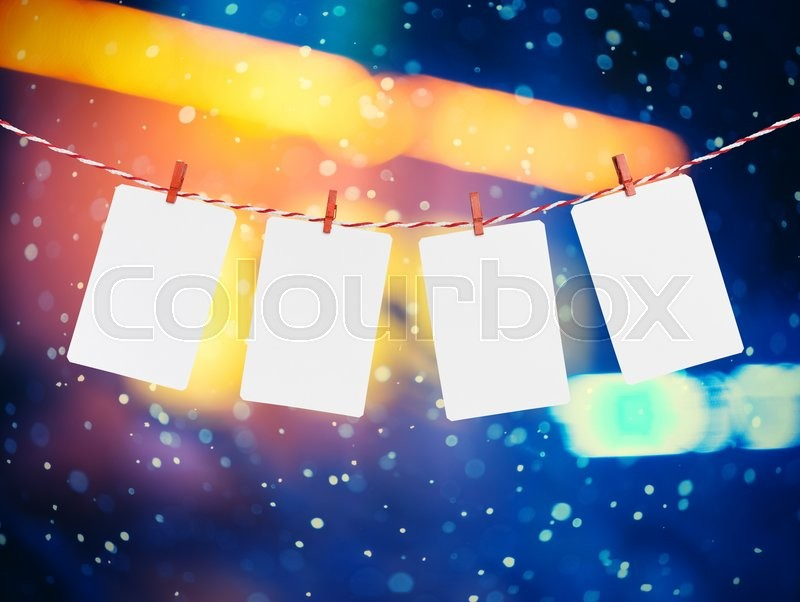 Stock image of 'Blank paper or photo frames hanging on the red striped rope. Snowfall background, Template for your design.'