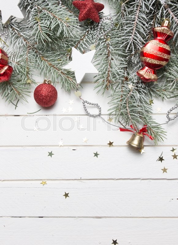 Stock image of 'Christmas or New Year decoration background: fur-tree branches, colorful glass balls, decoration and glittering stars on white wooden background, top view, copy space.'