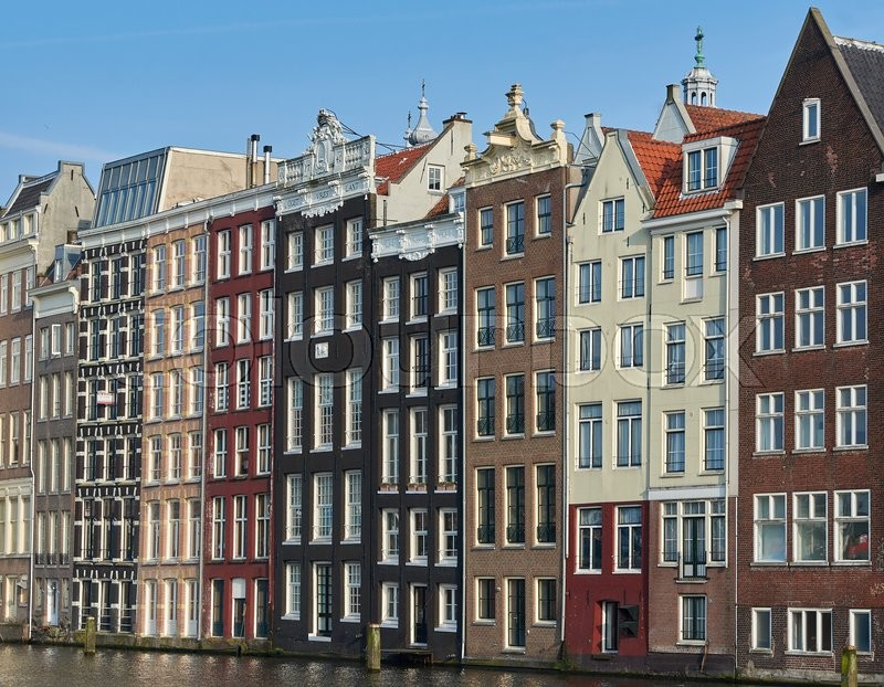 Stock image of 'Amsterdam, Netherlands – March 10, 2016: Canal houses in Amsterdam, with blue skies in the background'