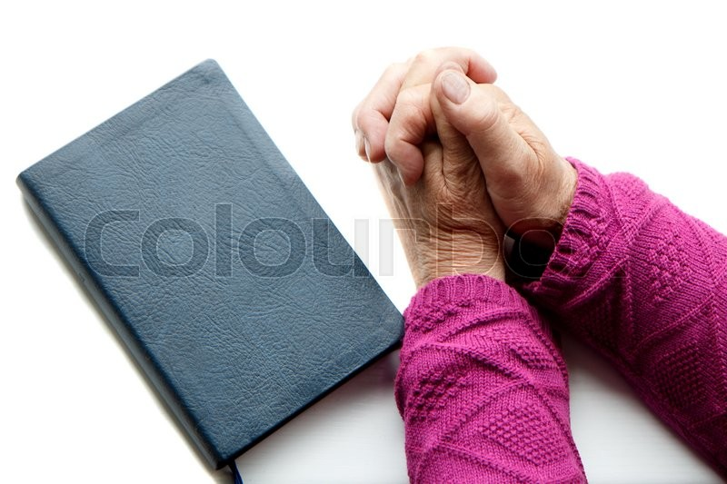 Stock image of 'An old person praying with the Holy Bible by her'