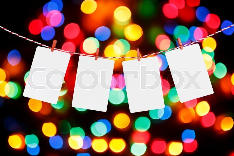 Stock image of 'Blank paper or photo frames hanging on the red striped rope. Blurred defocused multi color lights background, Template for your design.'