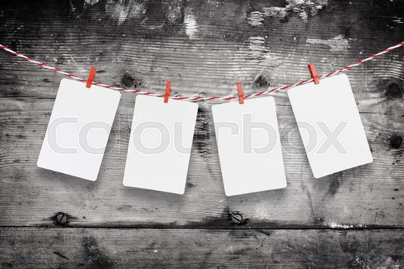 Stock image of 'Blank paper or photo frames hanging on the red striped clothesline . On wooden background. Template for your text'
