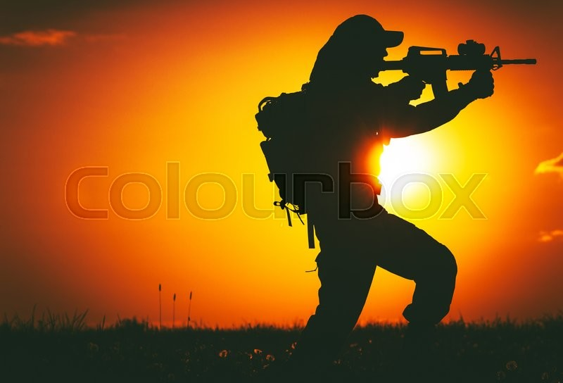 Stock image of 'Army Trooper with Assault Rifle in Mission. Military Mission at Sunset. Military Concept.'