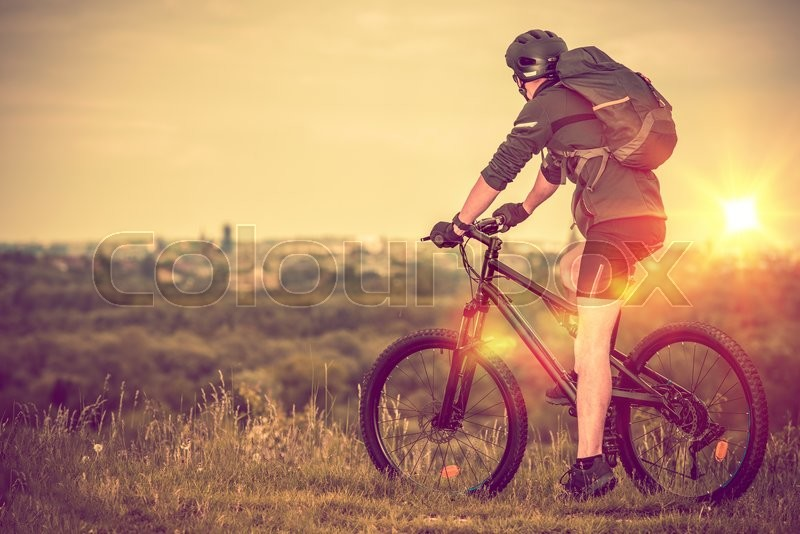 Stock image of 'Bike Trip with City View. Scenic Bike Trail. Caucasian Men on the Bike.'