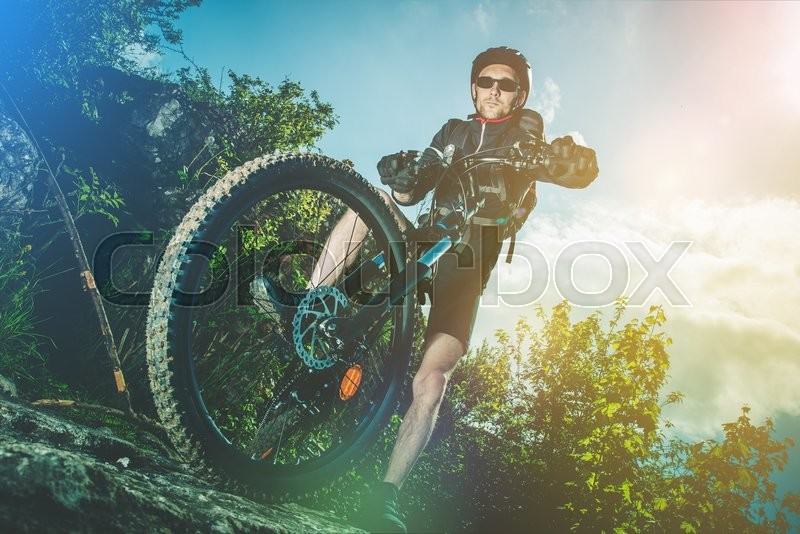 Stock image of 'Extreme Bike Ride Sport. Caucasian Biker on His Mountain Bike Riding on the Rocks.'