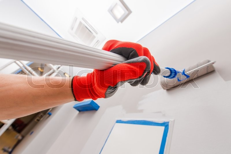 Stock image of 'Room Interior Painting by Telescoping Roller Painter.'