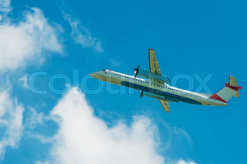 Stock image of 'Turboprop Jet Airplane Traveling. Airplane on the Cloudy Blue Sky.'
