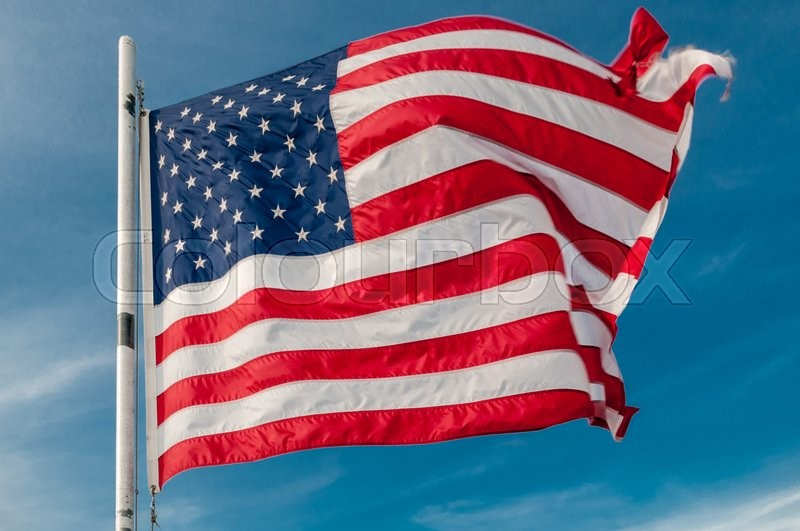 Stock image of 'American flag against bright blue sky'