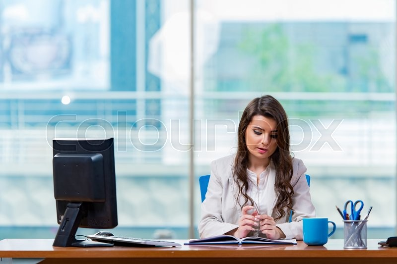 Stock image of 'Businesswoman sitting at the office desk'