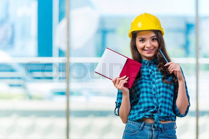 Stock image of 'Woman builder taking notes at construction site'