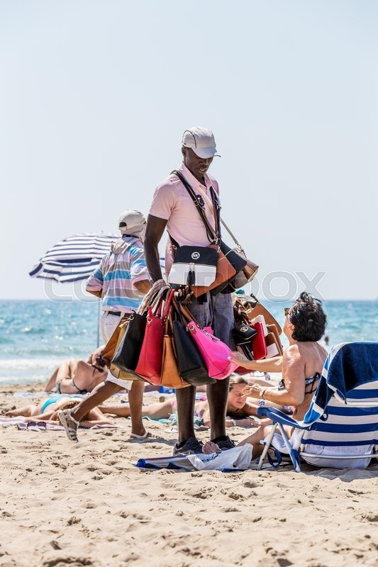 Editorial image of 'Alikante, Spain- June 4, 2016: An illegal immigrant, negro, from Africa sells fake bags on the beach in Spain'