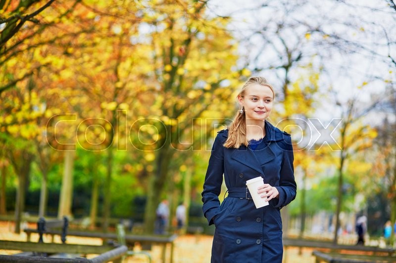 Stock image of 'Beautiful young woman in the Luxembourg garden of Paris on a fall day, drinking coffee to go'