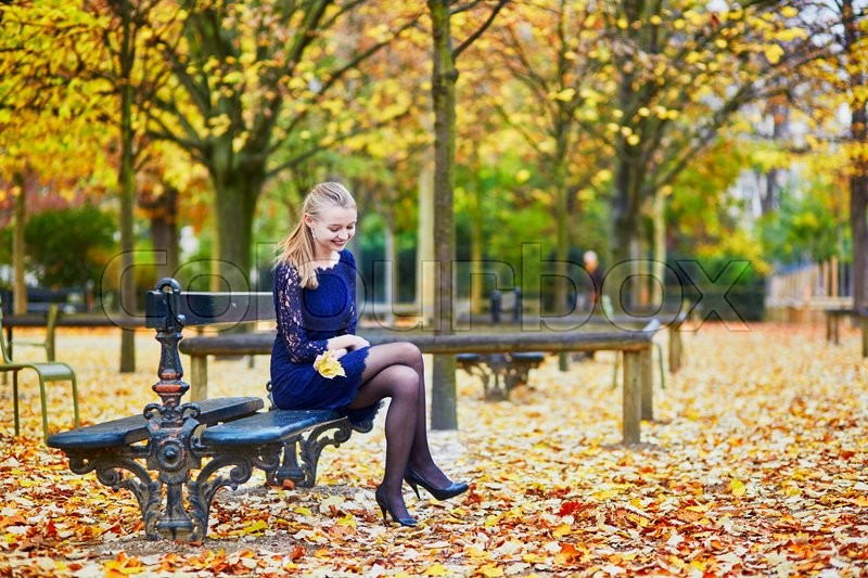 Stock image of 'Beautiful young woman in blue dress in the Luxembourg garden of Paris on a fall day'