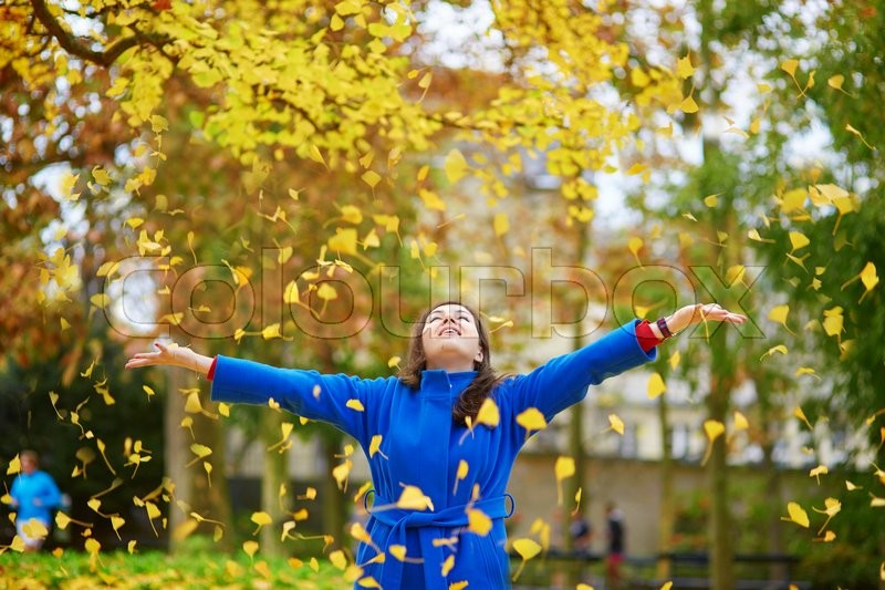 Stock image of 'Beautiful young tourist in Paris on a fall day in the Luxembourg garden and throwing colorful autumn leaves'
