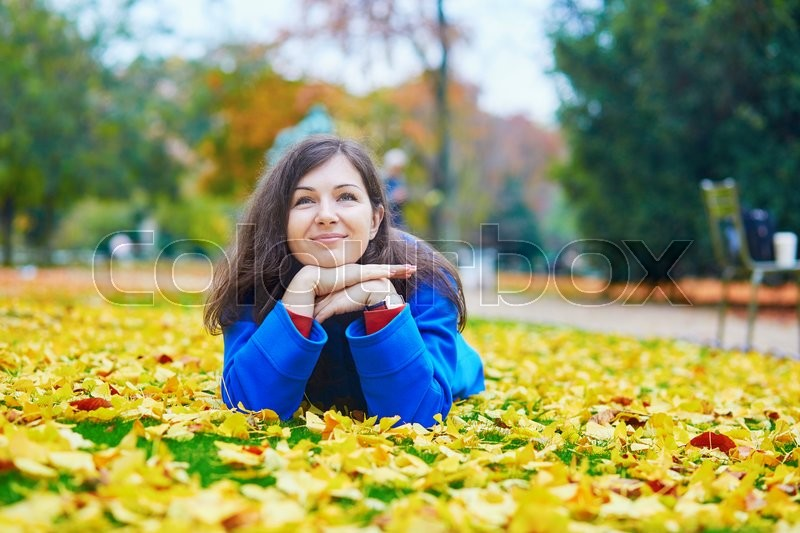 Stock image of 'Beautiful young tourist in Paris on a fall day, laying on the ground in the Luxembourg garden with colorful autumn leaves'