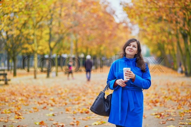 Stock image of 'Beautiful young woman in Paris on a fall day with tea or coffee to go'