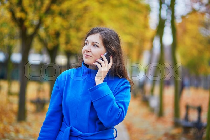 Stock image of 'Beautiful young woman in Paris on a fall day with mobile phone'