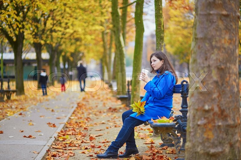 Stock image of 'Beautiful young girl in the Luxembourg garden of Paris on a fall day, with coffee or tea to go'