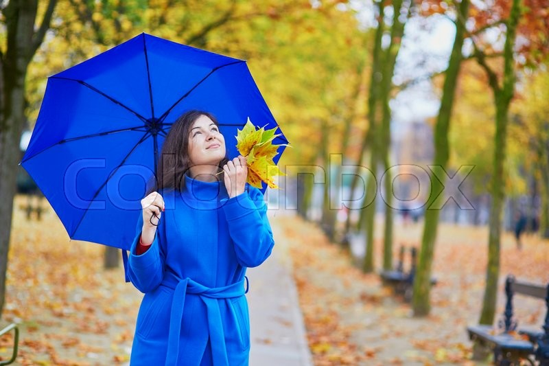 Stock image of 'Beautiful young woman in Paris on a fall day with blue umbrella'