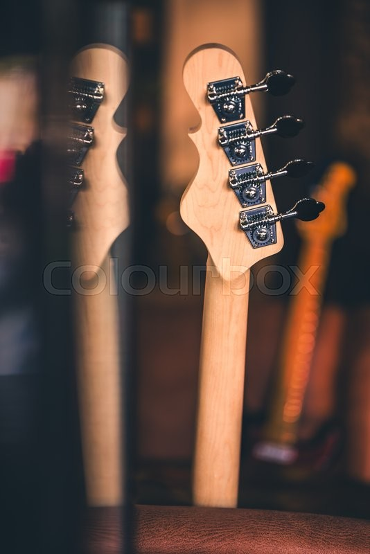 Stock image of 'Detail of Bass Guitar Head and Neck with Reflection. Other Guitar Necks in Background. Vintage Filter. Bass Guitar Still Life. Music Background.'