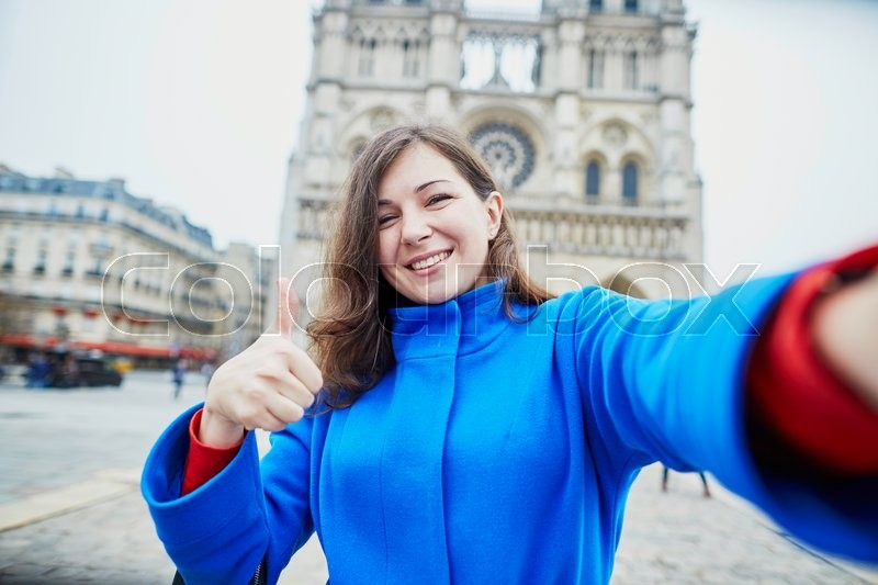 Stock image of 'Beautiful young tourist in Paris, making funny selfie near Notre-Dame cathedral'
