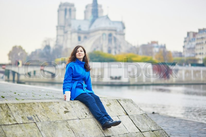 Stock image of 'Beautiful young tourist in Paris on a fall day, drinking coffee to go'