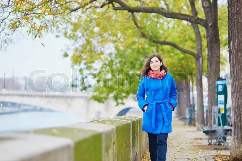 Stock image of 'Beautiful young tourist in Paris on a fall day, walking near the river Seine'