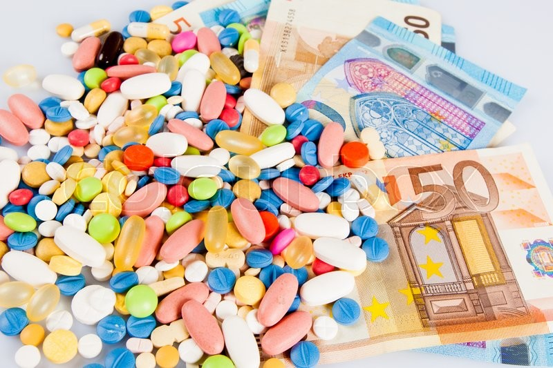 Stock image of 'Pills of different colors on money'