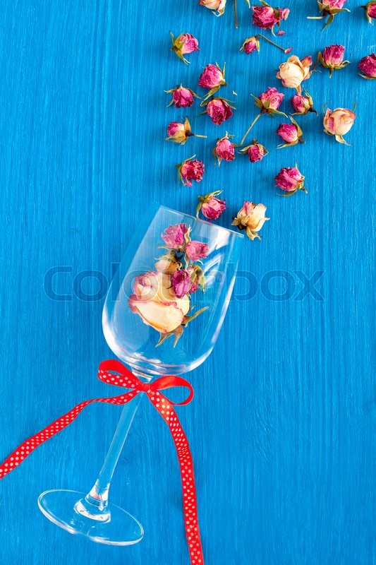 Stock image of 'Dried pink roses in a glass goblet on a blue background. Concept card with space for your text or wallpaper background.'
