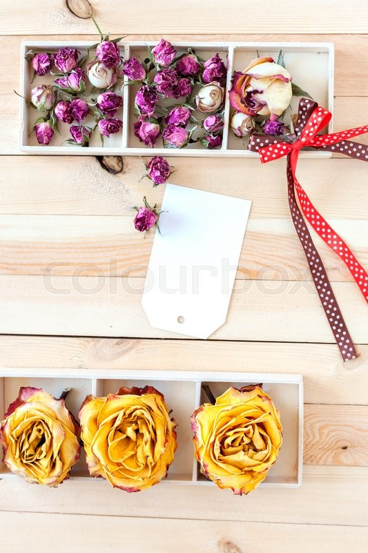 Stock image of 'Concept card with space for your text or wallpaper background. Dried yellow and pink roses in boxes on a wooden background.'