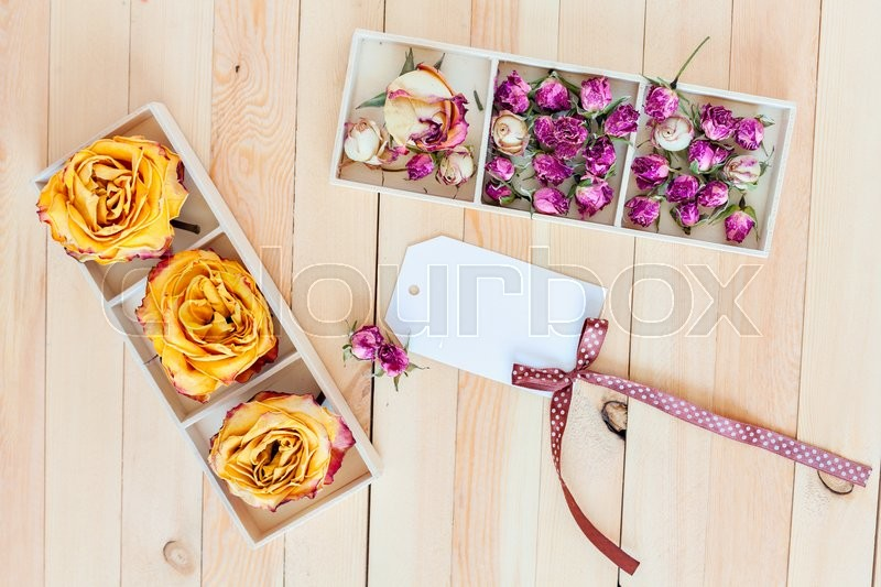 Stock image of 'Dried yellow and pink roses in boxes on a wooden background. Concept card with space for your text or wallpaper background'