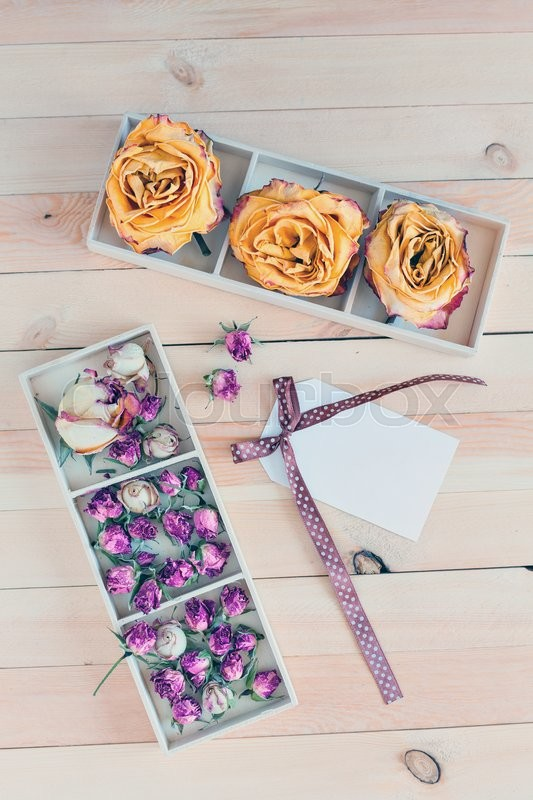 Stock image of 'Dried yellow and pink roses in boxes on a wooden background. Concept card with space for your text or wallpaper background.'