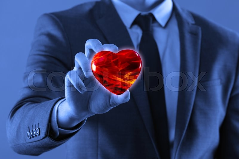 Stock image of 'Businessman holding red heart in medical concept'