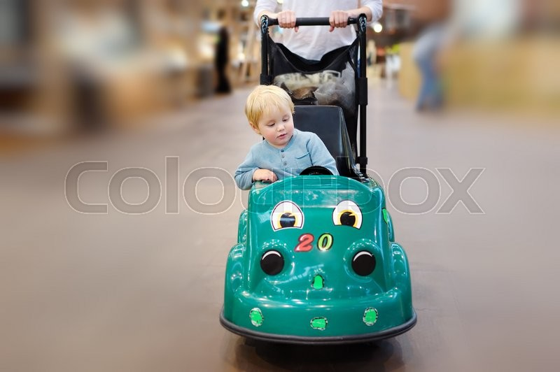 Stock image of 'European toddler boy sitting in the shopping cart made as toy car'