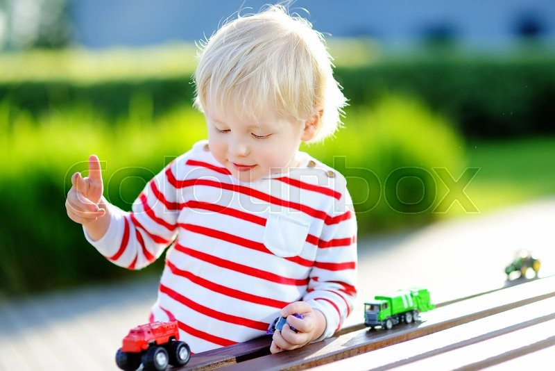 Stock image of 'Cute toddler boy playing with toy cars outdoors at warm summer day'