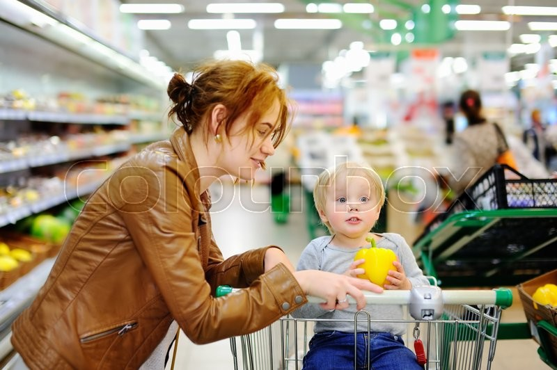 Stock image of 'Young mother and her cute toddler son in a food store or a supermarket'