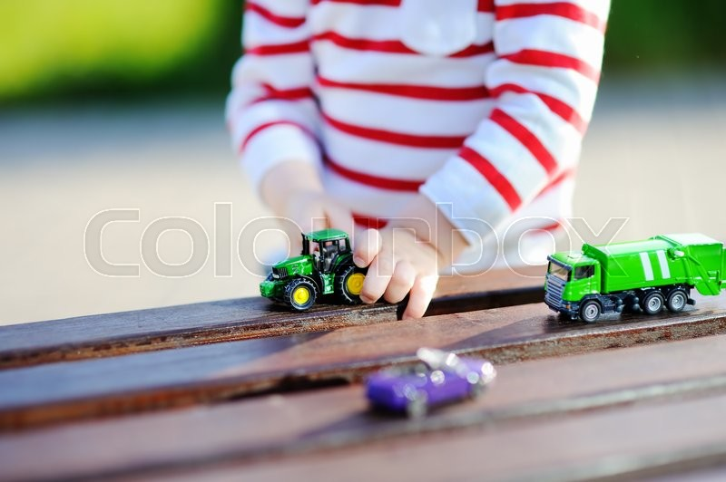 Stock image of 'Toddler boy playing with toy cars outdoors at warm summer day'