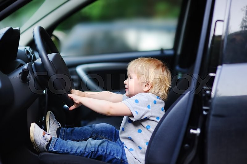 Stock image of 'Portrait of cute little boy playing in fathers car'