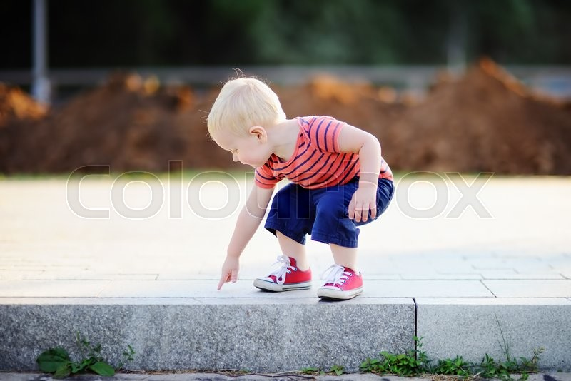 Stock image of 'Toddler boy playing outdoors at warm summer day'
