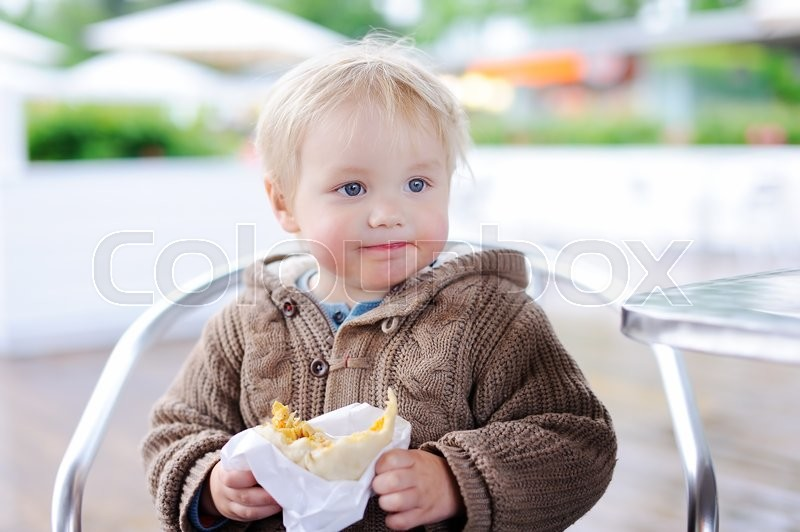 Stock image of 'Cute toddler boy eating fastfood in outdoors cafe'