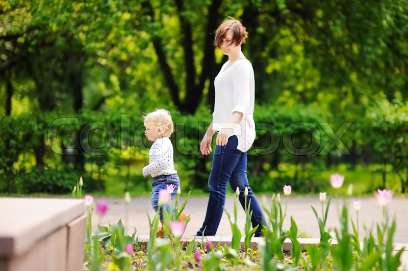 Stock image of 'Beautiful middle aged woman and her adorable little grandson walking in sunny park'