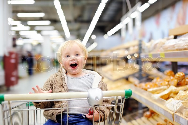 Stock image of 'Cute toddler boy sitting in the shopping cart in a food store or a supermarket'