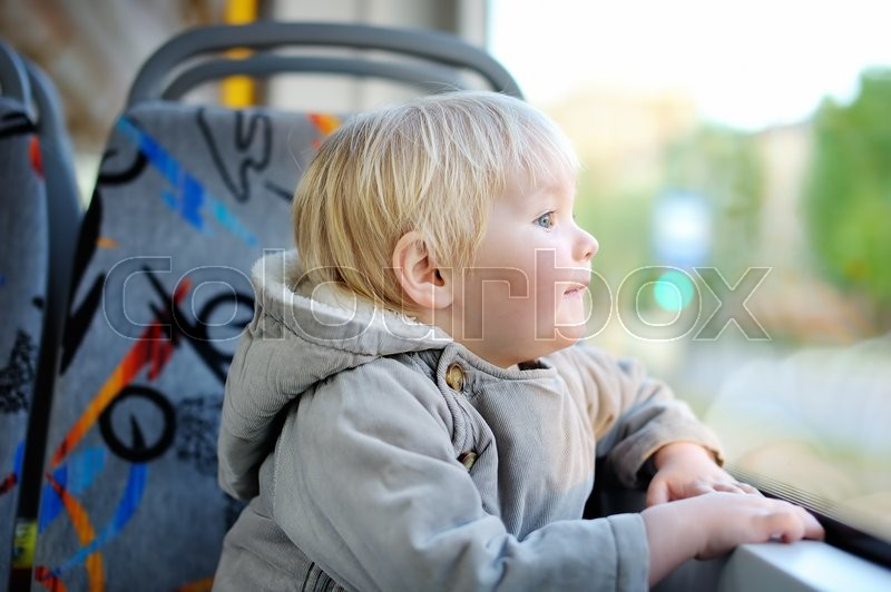 Stock image of 'Portrait of cute toddler boy looking out train or tram window'