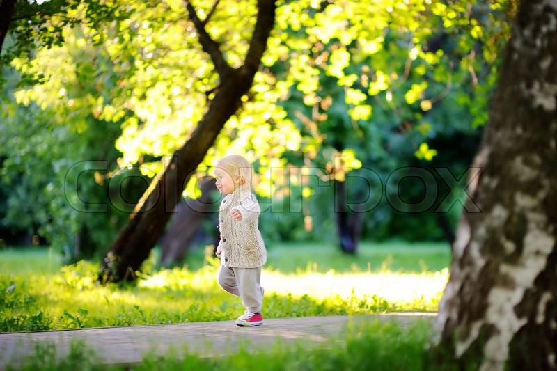 Stock image of 'Toddler boy running in the park at the spring or summer day'
