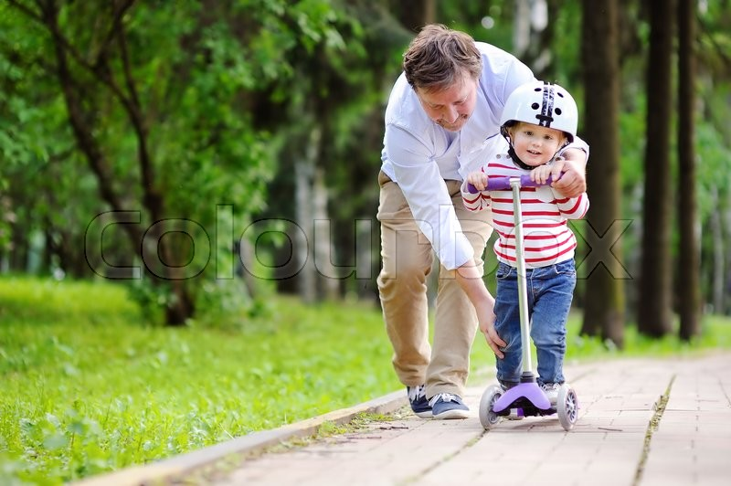 Stock image of 'Middle age father showing his toddler son how to ride a scooter in a summer park'