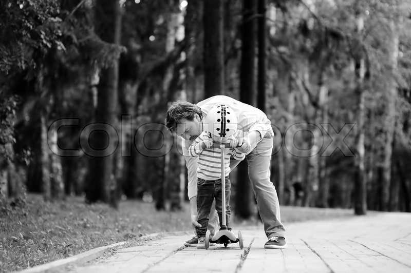 Stock image of 'Black and white photo of middle age father showing his toddler son how to ride a scooter in a summer park'